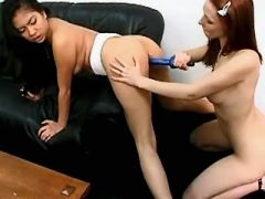 Two interracial babes have fun with dildos on sofa