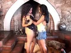 Young black lesbians relax with dildo by fireplace